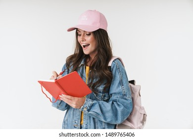 Photo of pretty student girl wearing cap smiling while writing down notes at diary book isolated over white background