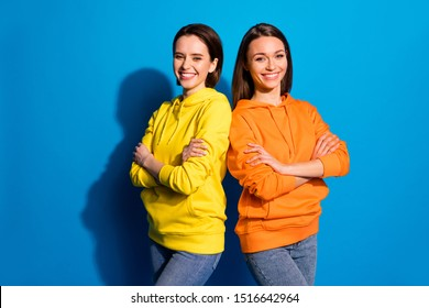 Photo of pretty two girlfriends lady standing back-to-back in good mood crossing arms wear casual bright hoodies and jeans isolated blue color background