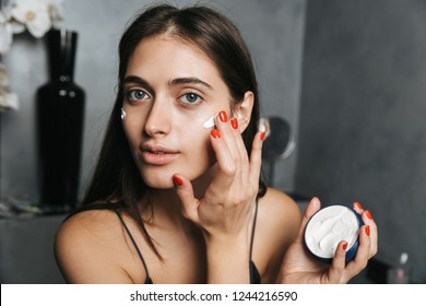 Photo of pretty woman with long dark hair standing in bathroom and applying moisturizing cream on body