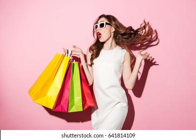 a0c34a7d3 Photo of a pretty young brunette woman in white summer dress wearing  sunglasses posing with shopping