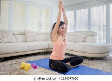 Photo of a pretty young woman practicing yoga and meditation while sitting on mattress at home