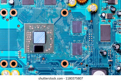 Photo of processor or central processing unit (CPU) in electronic device,  there  also show few microchip and yellow capacitor on blue printed circuit board (PCB)