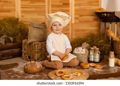 Photo project Little baker. A little boy dressed like a baker in apron and baker's cap posing.