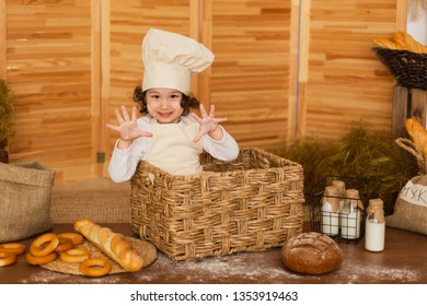 Photo project Little baker. Little girl dressed like a baker and wearing an apron and a baker's cap. She is smiling and happy.