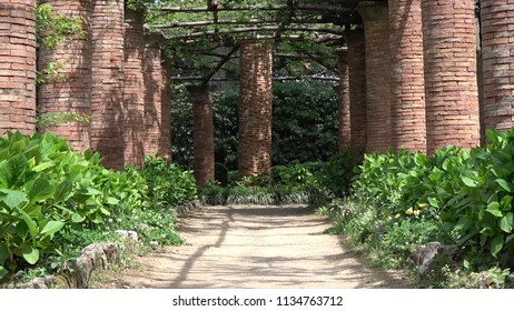 Photo of public park walking trail and masonry pillars left and right slowly zooming out from end of path showing more masonry build pillars and plants beautiful maintained park