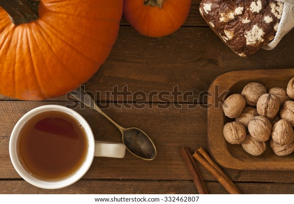 Photo of pumpkins, bread, walnuts, cinamon and old vintage spoon on wooden table