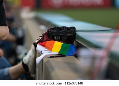 A photo of a rainbow towel next to a baseball glove at a baseball game.