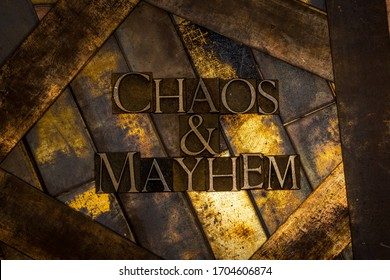 Photo of real authentic typeset letters forming Chaos and Mayhem text on vintage textured grunge copper background