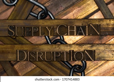 Photo of real authentic typeset letters forming Supply Chain Disruption text with steel chain on vintage textured grunge copper and gold background