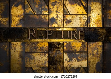 Photo of real authentic typeset letters forming Rapture text on vintage textured grunge copper and gold background
