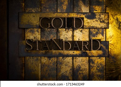 Photo of real authentic typeset letters forming Gold Standard text on vintage textured grunge copper and gold background