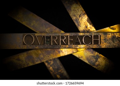 Photo of real authentic typeset letters forming Overreach text on vintage textured grunge copper and black background