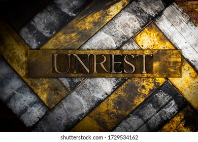 Photo of real authentic typeset letters forming Unrest text on vintage textured grunge copper and black background