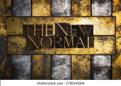 Photo of real authentic typeset letters forming The New Normal text on vintage textured grunge copper and black background