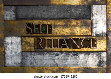 Photo of real authentic typeset letters forming Self Reliance text on vintage textured grunge silver and gold background