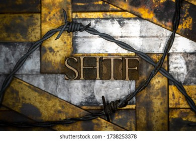 Photo of real authentic typeset letters forming capitalized SHTF text with barb wire on vintage textured grunge copper background
