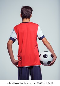 Photo of rear view teen boy in sportswear holding soccer ball - posing at studio
