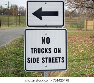 Photo of a rectangular traffic information sign instructing trucks to not use side streets