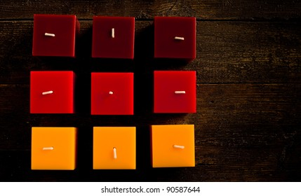 photo of red christmas candles on wooden table highlighted by spot