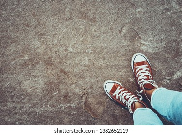Photo of a red gumshoes over dirty sand background, cool teenagers shoes, urban youth lifestyle