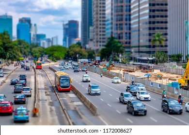 Photo of red public transport bus and many other vehicle, crossing primary road in Jakarta, Indonesia, captured in Jend. Sudirman street, with minature or tilt-shift effect.