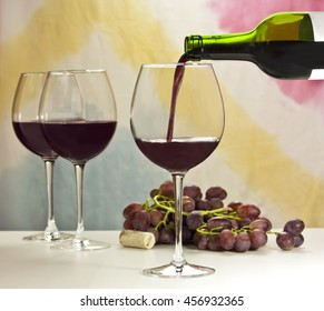 Photo of red wine being poured into glass from bottle; there are more blurred full wine glasses in the background, and also out of focus grapes and year 2014 cork; the background is abstract stains