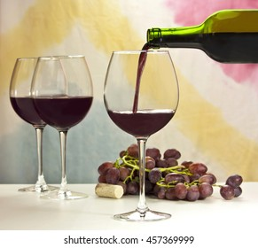 Photo of red wine being poured into glass from bottle; there are more blurred full wine glasses in the background, and also out of focus grapes and cork; the background is abstract stains