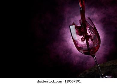 Foto von Rotem Wein in einem Weinglas mit abstraktem Hintergrund