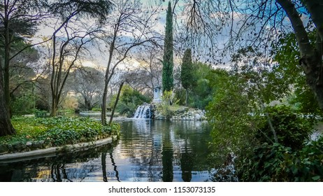 A photo of the reflection in the water of a small lake or pond of a variety of trees and plants, and a beautiful artificial waterfall in the famous Parque de El Capricho, in Madrid, Spain, Europe.