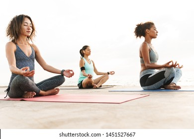 Photo of relaxed multiethnic sportswomen in tracksuits meditating and doing zen gestures while sitting on yoga mats by seaside in morning