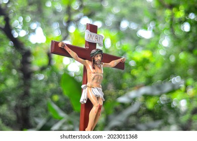 Photo of a religious Catholic figurine Jesus in a cross altar outdoors with a boke background