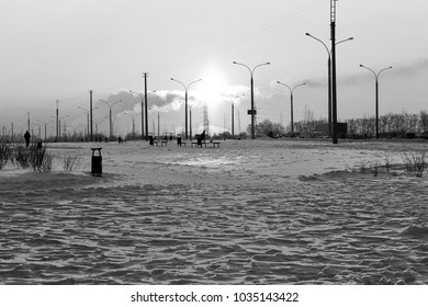A photo representing an industrial roman concept - beautiful and peaceful dawn deserted landscape with transmission lines and sun reflexions on the snow