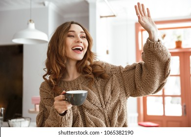 Photo of resting relaxed woman sitting at table in cafeteria and waving hand to friend while drinking cup of tea or coffee
