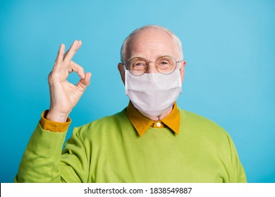 Photo of retired grandpa raise hand fingers showing okey wear white face mask isolated blue color background