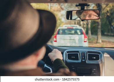 Photo of retired old man drive sit seat reflecting rare view mirror look road wear brown jacket headwear spectacles inside car