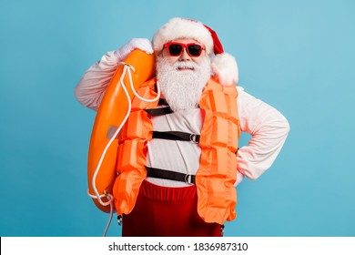 Photo of retired old man grey beard yacht tour liner captain hold inflatable circle prepare long swim summer wear life vest santa x-mas costume sunglass cap isolated blue color background