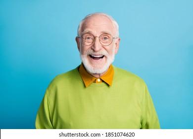 Foto des pensionierten alten Mannes Open Mund glänzendes Lächeln aufgeregt tragen Gläser grüner Pullover einzeln blauer Hintergrund
