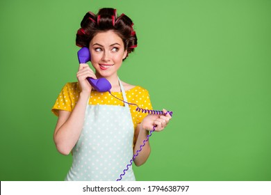 Photo of retro vintage girl call telephone cord hear telesales ads look copyspace bite lips teeth wear style trendy yellow dotted dress skirt hair rollers isolated green color background