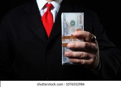 Photo of a rich businessman in black siut with red tie holding a money pack.