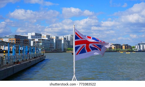 Photo from river clipper with UK flag waving cruising in river Thames on a spring morning, London, United Kingdom