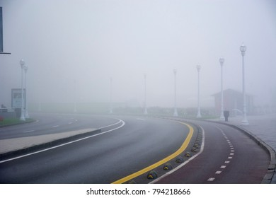Photo of a road with fog and several streetlights