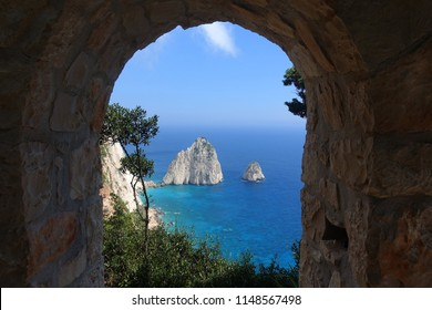 Photo of rocky steep cliff white seascape with beautiful turquoise sea and two small islets called Mizithres in West side of Zakynthos island, Ionian islands, Greece
