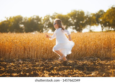 Photo of a runnig girl, on a golden sun light, in a wheat field