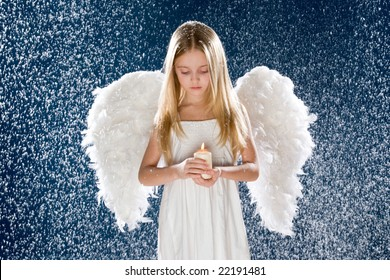 Photo of sad angel holding burning candle while standing under snowfall