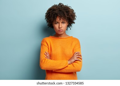 Photo of sad displeased young lady keeps arms crossed, upset to hear offensive words, has gloomy facial expression, wears orange jumper, isolated over blue background. Negative feelings concept