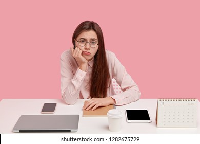 Photo of sad European woman holds chin, looks in discontent, wears round spectacles and elegant shirt, doesnt want to work, uses modern gadgets, isolated over pink background. Perfectionism.