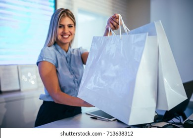 Photo of a saleswoman handing over shopping bags to the customer in the store.