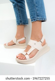 Photo of sandals on women's feet on a white background