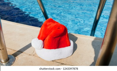 Photo of Santa Claus left his hat outdoor swimming pool. Concept of travel and tourism on Christmas, New Year and winter holidays.