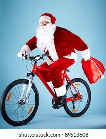 Photo of Santa Claus with red sack riding bike